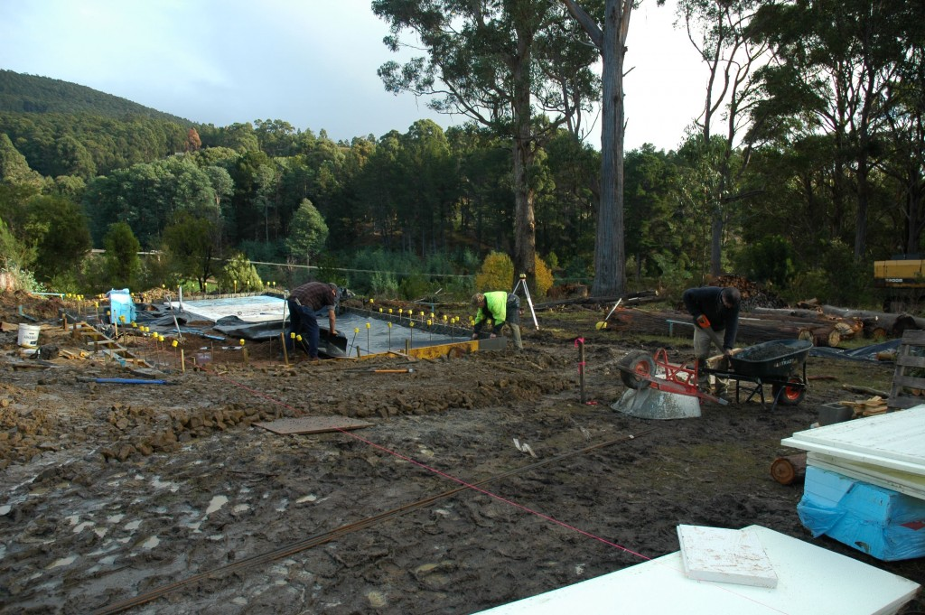 Steve and Greg laying the plastic sheet for the concrete to be poured over; Pete using the wheelbarrows as a makeshift sawhorse