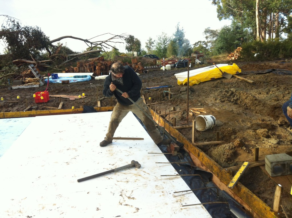 Iron Man! Pete bending the steel reinforcing from the footings back so it can be tied into the slab