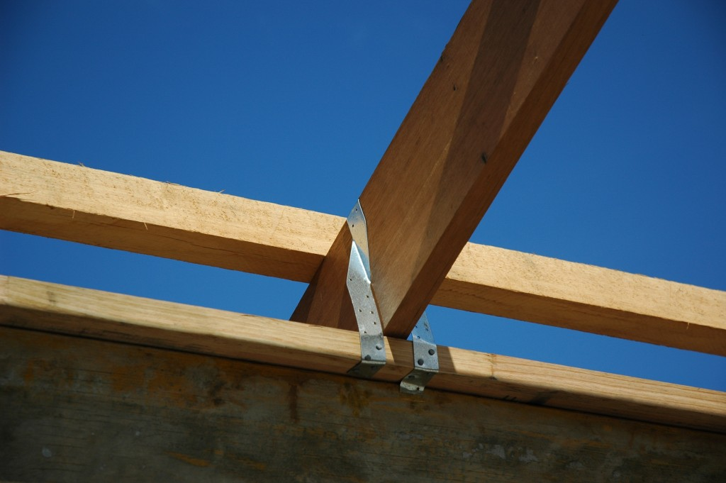 The trusses are tied down to the top plate of the wall with metal strap bracing
