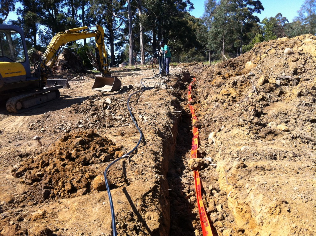 Unwinding the poly water pipe to lay in the trench with the warning tape
