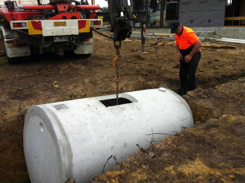 Second time lucky: lowering the septic tank into the hole for the second time