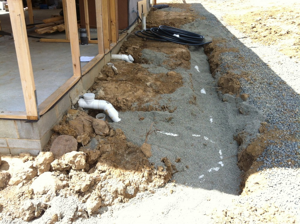 Thar she flows: all of the plumbing coming out of the rear of the house