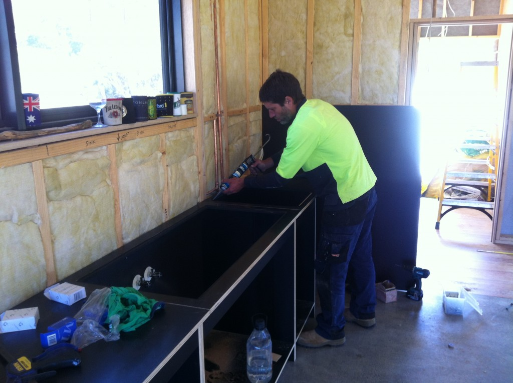 Gunning it: Mark caulking the joins in the bench tops