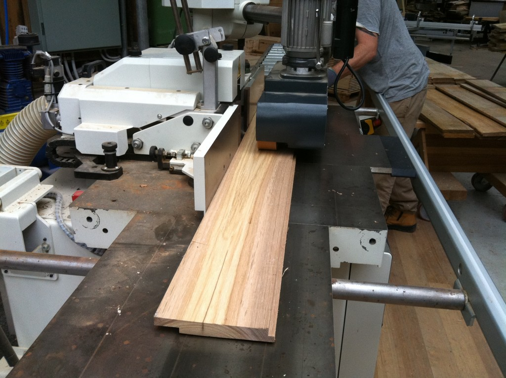Passing through: Adam feeding a board through the profile machine to cut the rebate to create the ship lap