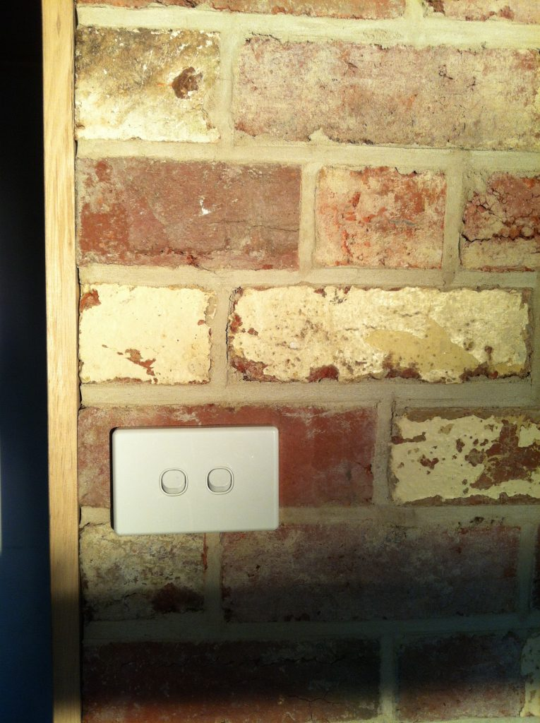 Rough and refined: the light switch installed on the recycled brick wall