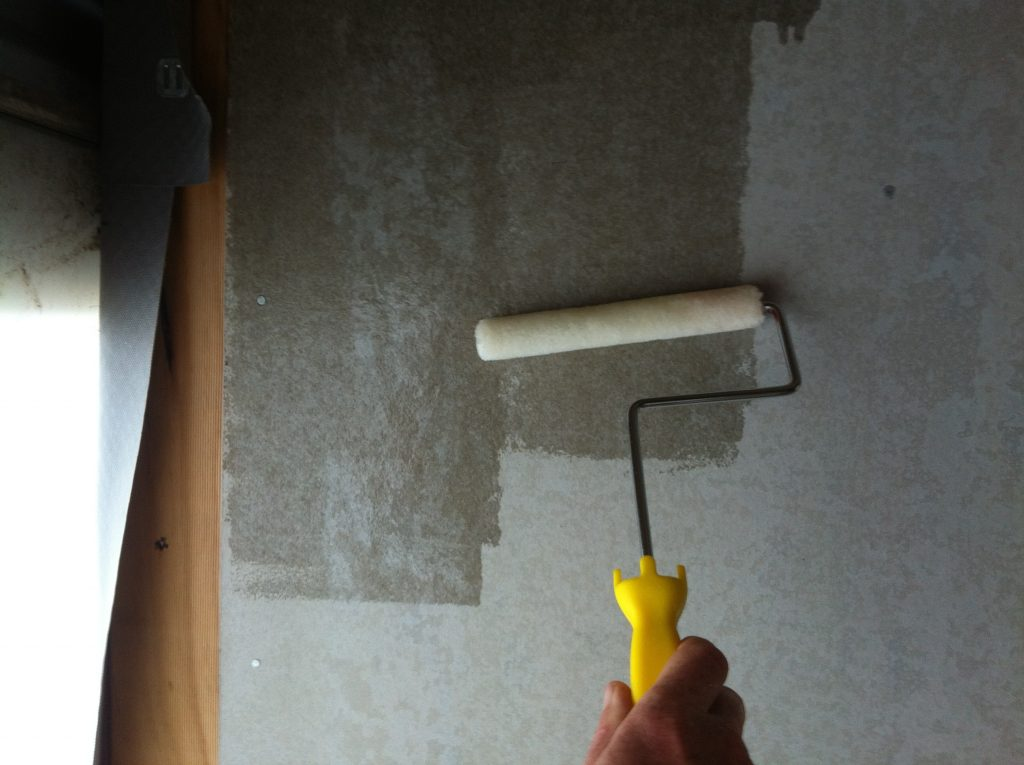 Roller derby: rolling the polyurethane onto the bathroom cement sheet wall